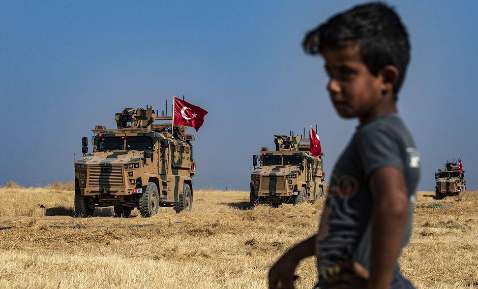 Un niño sirio observa a vehículos militares turcos, patrullando la aldea siria de al-Hashisha. El gobierno turco alista un ataque militar en el norte de Siria. (Foto: AFP)