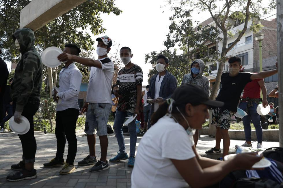 Personas que plenean llegar a pie a Tarapoto hacen parada para descansar en parque de Santa Anita. (Foto: Renzo Salazar/GEC)