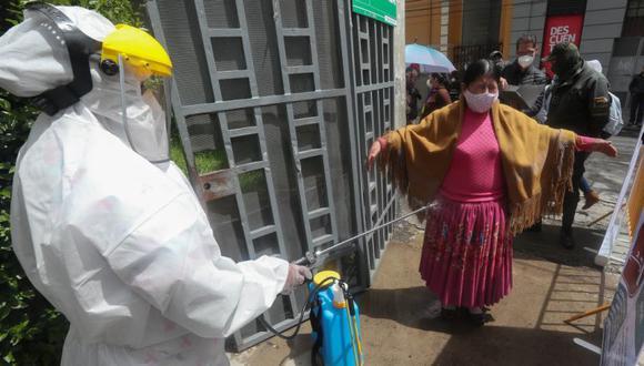 Un miembro del Sistema Departamental de Salud desinfecta a una mujer en la entrada del coliseo Julio Borelli en La Paz (Bolivia). EFE/ Martín Alipaz/Archivo