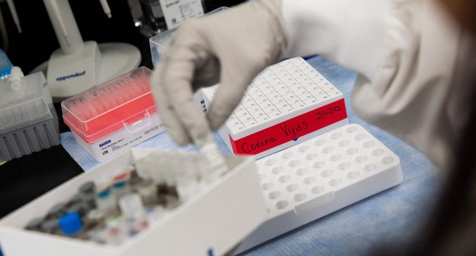 Doctora levanta un vial con una posible vacuna contra el coronavirus (COVID-19). (AFP / ANDREW CABALLERO-REYNOLDS).