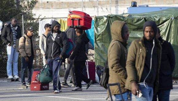 Migrantes cargan con sus pertenencias mientras abandonan el campamento de Baobab, instalado frente a la estación de Tiburtina, en Roma. (Foto referencial: EFE)