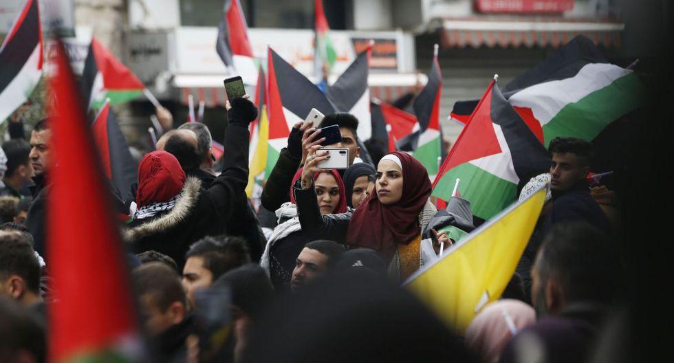 Una mujer se toma un selfie mientras los palestinos ondean banderas nacionales durante una manifestación contra una propuesta de paz negociada por Estados Unidos. (AFP).