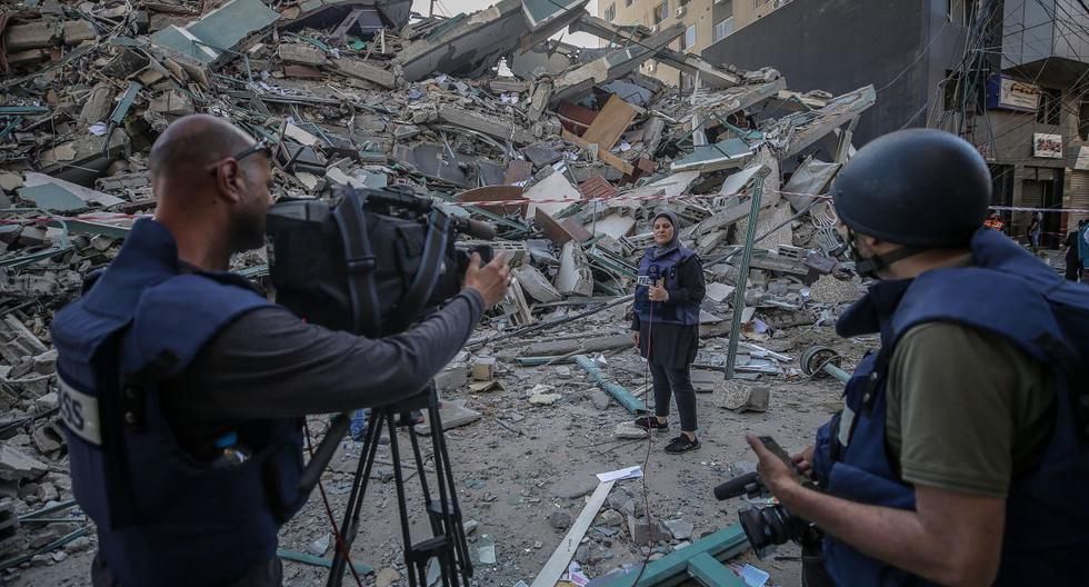 El equipo de televisión palestino trabaja junto a los escombros de su oficina destruida, la torre Al-Jalaa, que alberga apartamentos y varios medios de comunicación, incluidos The Associated Press y Al Jazeera, en Gaza, el 15 de mayo de 2021. (EFE/EPA/HAITHAM IMAD).