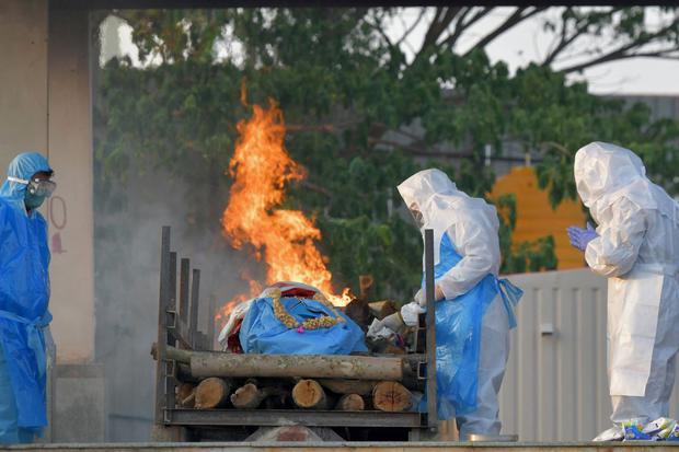 Los familiares que usan equipo de protección realizan los ritos finales de una víctima que murió por el coronavirus Covid-19 en un crematorio en Bangalore, India, el 26 de abril de 2021. (Foto: Manjunath Kiran / AFP).
