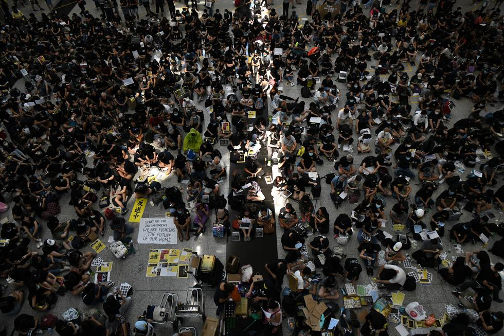 """""""No somos agitadores, esto es una tiranía"""", gritaban los manifestantes en aeropuerto de Hong Kong, algunos de ellos equipados con sus ya emblemáticas máscaras y cascos de obra. (Fotos: AFP)"""