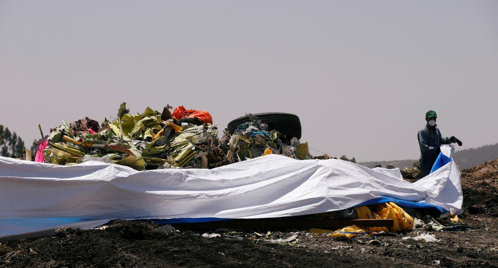 Un hombre cubre los restos del accidente de Ethiopian Airlines. (Foto: Reuters)