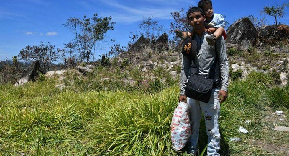 César, un policía municipal venezolano, llega con su hijo a hombros procedente de Santa Elena de Uairén, a 20 kilómetros de Pacaraima.(Foto: AFP)