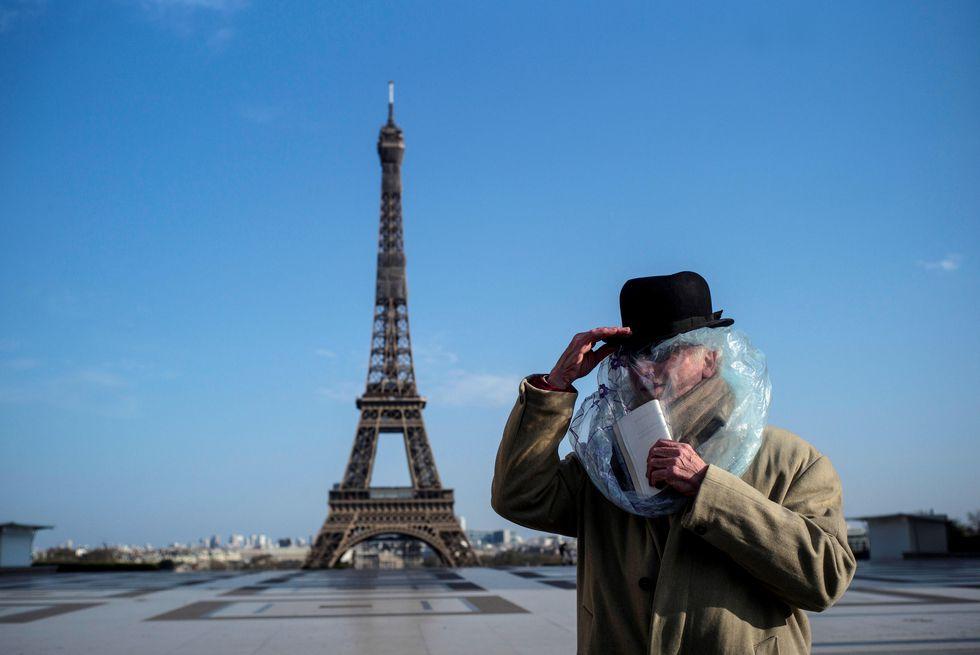 Un hombre cubierto con una bolsa de plástico lee un libro frente a la Torre Eiffel en París. (EFE/Julien de Rosa).