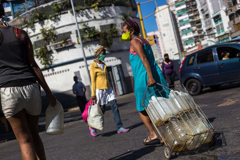 Personas usan mascarillas como medida preventiva contra la pandemia mundial de coronavirus mientras llevan latas de agua recolectadas de una tubería de la calle en Caracas. (Foto: AFP/Cristian Hernández)