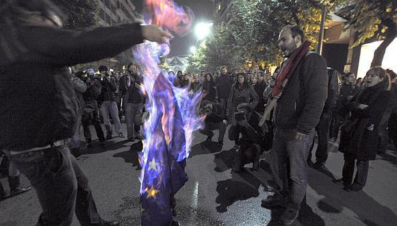Manifestantes queman una bandera de la UE en protesta por su manejo de la crisis. (AP)