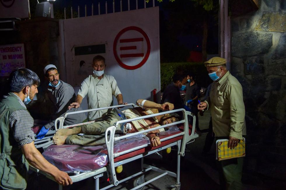 Personal médico y hospitalario lleva a un herido en una camilla para recibir tratamiento después de dos poderosas explosiones en Kabul (Afganistán), el 26 de agosto de 2021. (Wakil KOHSAR / AFP).