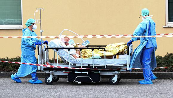 Trabajadores sanitarios con trajes protectores y máscaras faciales llevan a un paciente de coronavirus en Hospital Brescia, Italia. (Foto: EFE)