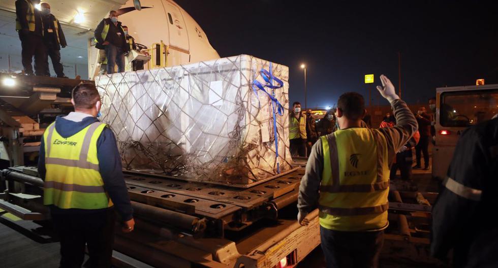 Los funcionarios trasladan el segundo lote de la vacuna Sinopharm desde China, tras su llegada al Aeropuerto Internacional de El Cairo, en El Cairo, Egipto, el 23 de febrero de 2021.  (EFE/EPA/KHALED ELFIQI).