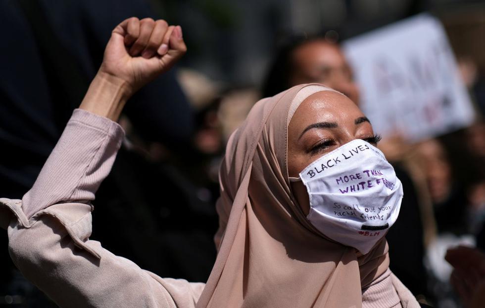 Una mujer con una máscara facial levanta el puño durante una protesta contra la muerte del hombre afroamericano George Floyd, en la plaza Hermannplatz en el distrito de Neukoelln, Berlín, Alemania. (REUTERS / Christian Mang)