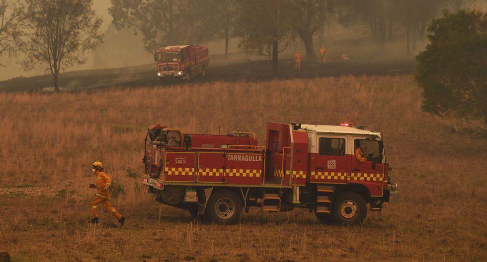 Los bomberos trabajan para apagar las llamas cerca de la ciudad de Taree, a unos 350 kilómetros al norte de Sydney. (AFP)