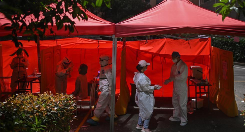 Imagen referencial. Un trabajador médico (espalda izquierda) toma una muestra de un hisopo de una mujer para ser examinada por el coronavirus (COVID-19) en Wuhan, provincia central de Hubei en China, el 19 de mayo de 2020. (HÉCTOR RETAMAL / AFP).