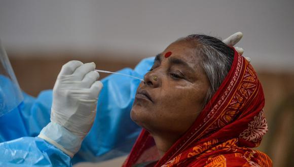 Un oficial de salud recoge una muestra nasal de una mujer para una prueba de COVID-19 en un centro de colección en el área de Samarnagar en Siliguri el 9 de setiembre. (Foto de DIPTENDU DUTTA / AFP)