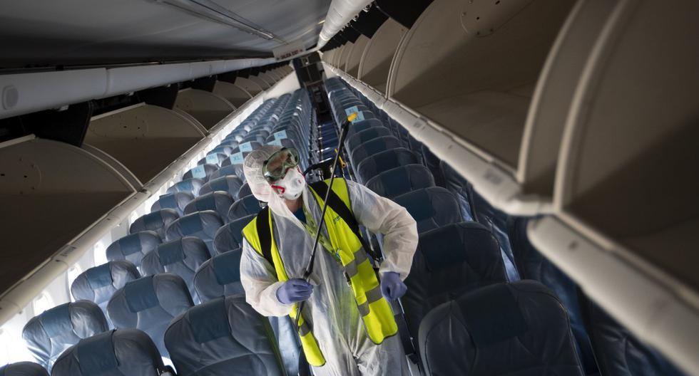 Imagen referencial. Un empleado, que usa equipo de protección, realiza una desinfección dentro de un avión de Air Europa en el aeropuerto de Son Sant Joan en Palma de Mallorca. (JAIME REINA / AFP).