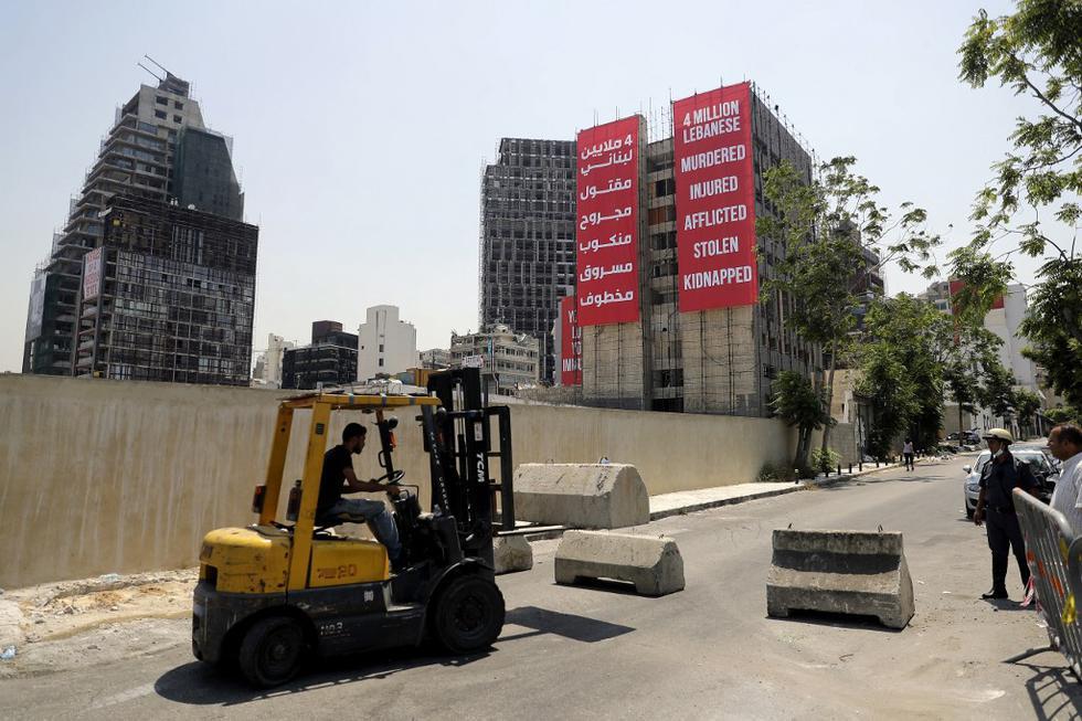 Un camión bloquea una carretera que conduce a la carretera que da al puerto de Beirut con pancartas colgadas en un edificio dañado durante la explosión del puerto del año pasado al otro lado de la calle, como lo marca Líbano el 4 de agosto de 2021, un año desde que una explosión catastrófica devastó la capital Beirut. (Foto de JOSEPH EID / AFP)