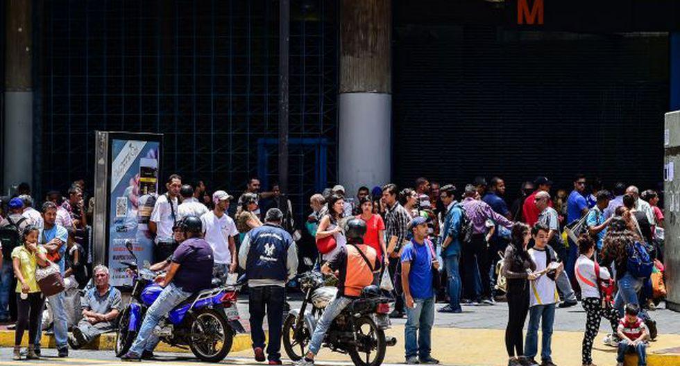 La gente espera afuera de una estación de metro durante un apagón en Caracas. Se estima que 2,3 millones de personas han huido de Venezuela hasta el pasado 1 de julio. (Foto: AFP)