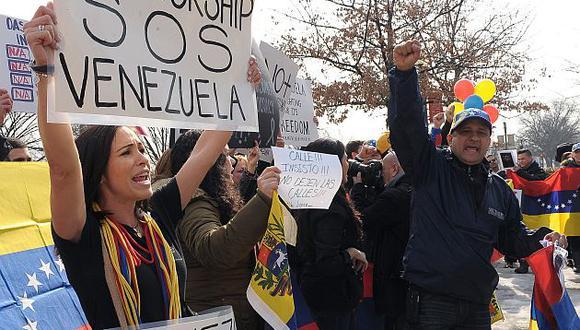 Decenas de personas protestan frente a la sede de la OEA, en Washington, por su silencio ante la situación en Venezuela. (EFE)