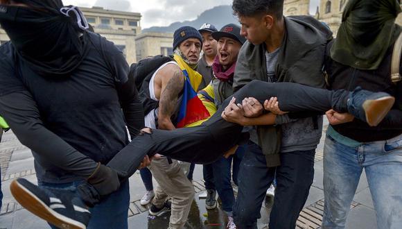 Manifestante herido es llevado por sus compañeros durante enfrentamientos por la huelga nacional convocada por estudiantes, sindicatos y grupos indígenas para protestar contra el gobierno del presidente colombiano Ivan Duque, en Bogotá. (Foto: AFP)