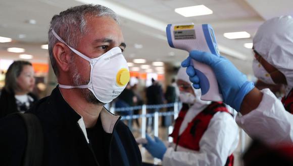Viajeros utilizan mascarillas en el Aeropuerto internacional Mariscal Sucre de Quito. El Ministerio de Salud Publica de Ecuador refuerza junto a su personal los controles sanitarios mediante la toma de temperatura, colocando alcohol en las manos, y brindando información sobre el coronavirus. (EFE).