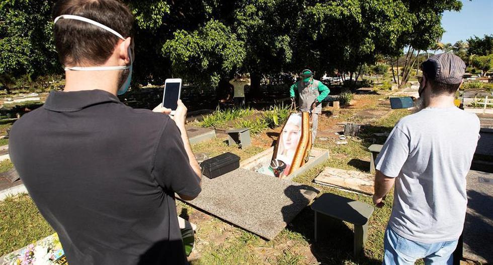 Trabajadores del cementerio Campo de Esperanza entierran una víctima de coronavirus este lunes, en Brasilia. (EFE/Joédson Alves)