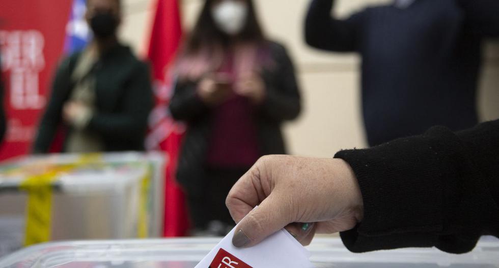 Un trabajador del servicio electoral muestra una boleta sellada en Santiago de Chile, antes de las elecciones del 15 y 16 de mayo para elegir alcaldes, concejales y una comisión para reescribir la constitución. (CLAUDIO REYES / AFP).