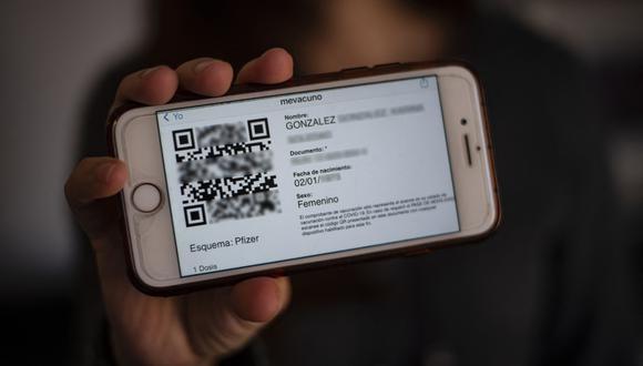 Una mujer muestra un 'pase de movilidad' en su teléfono móvil que le permite moverse por el país, incluso entre ciudades que están dentro y fuera de cuarentena en medio de la pandemia del coronavirus COVID-19, en Santiago, el 26 de mayo de 2021. ( Foto de MARTIN BERNETTI / AFP)