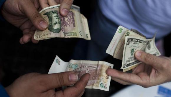 MÁS PESOS. Los argentinos están acostumbrados a realizar sus transacciones con pesos y dólares. (AP)