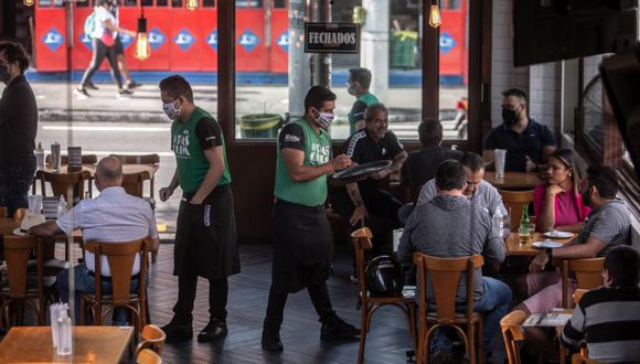 Servers wearing protective masks work at a restaurant in the Vila Madalena neighborhood of Sao Paulo, Brazil, on Monday, July 6, 2020. The mega-city, with some 20 million people in the greater metropolitan area, started reopening restaurants and bars Monday even as the virus explodes across much of the country. Photographer: Jonne Roriz/Bloomberg