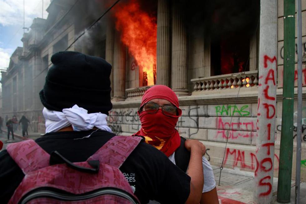 Cientos de manifestantes tomaron este sábado el Congreso de Guatemala y le prendieron fuego a varias oficinas hasta ser desalojados por fuerzas de seguridad y cuerpos de bomberos, que apagaron el incendio. (EFE/Esteban Biba)