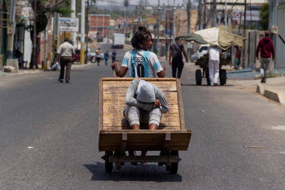 """En esta imagen se observa unos comerciantes en las inmediaciones del mercado """"Las Pulgas"""", en Maracaibo, Venezuela. Empujados por la necesidad, cientos de comerciantes mantuvieron sus actividades en un atiborrado mercado popular en Maracaibo, en el oeste de Venezuela, burlando las estrictas medidas que impuso el Gobierno el pasado marzo, y generando un foco de contagio que hizo saltar todas las alarmas en los últimos días. El brote se produce en un área de 120.000 metros cuadrados, en la ciudad de Maracaibo, en la que cientos de vendedores, la mayoría al aire libre, reciben diariamente a decenas de miles de compradores que hasta ahora habían ignorado un riesgo evidente. (EFE/ Henry Chirinos)"""