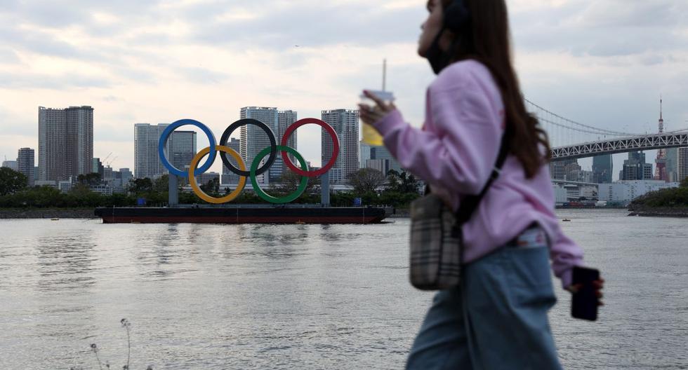 Una mujer pasa junto a los anillos olímpicos en el paseo marítimo de Odaiba en Tokio (Japón), el 12 de abril de 2021. (Yuki IWAMURA / AFP).