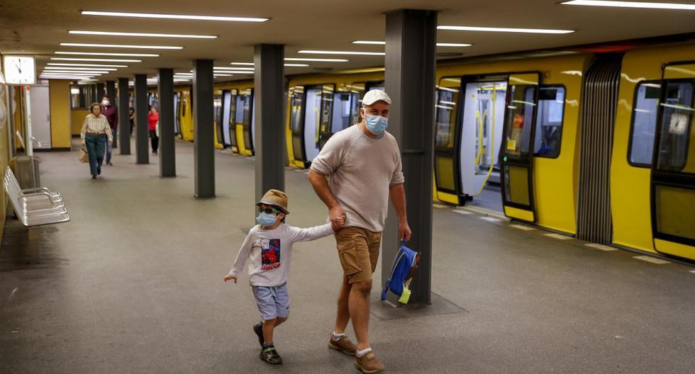 Un padre junto a su hijo usan máscaras de protección facial en la estación de metro Bahnhof Zoo, en Berlín. Se requerirán máscaras protectoras en el transporte público en la mayor parte de Alemania y en la capital, Berlín. (Odd ANDERSEN / AFP)