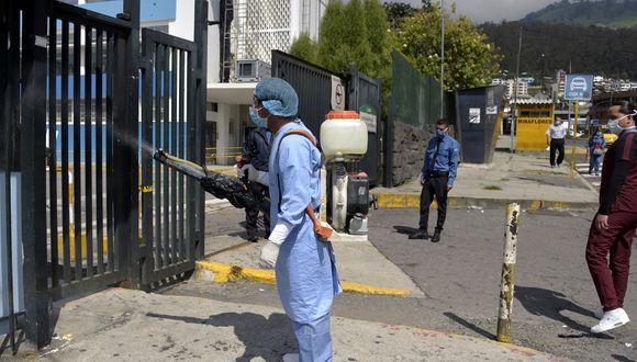 Un trabajador de la salud desinfecta la entrada de emergencia de un hospital en Quito, en medio de la pandemia de coronavirus Covid-19. (Foto: AFP/Rodrigo BUENDIA)
