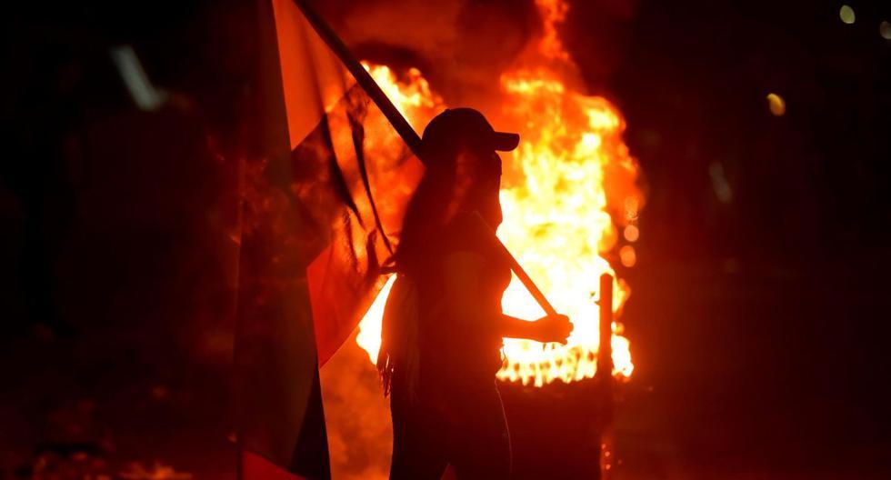 Fotografía del 3 de mayo de 2021 que muestra a un grupo de manifestantes que incendian llantas mientras bloquean vías durante las protestas en Cali, Colombia. (EFE/ Ernesto Guzmán Jr).