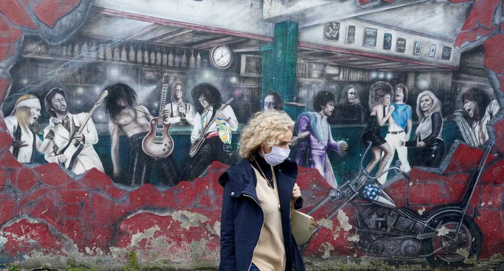 Una mujer con una mascarilla protectora pasa junto a un mural en una pared en Galway, Irlanda. (REUTERS/Clodagh Kilcoyne).