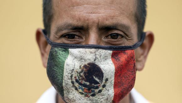 En esta foto de archivo tomada el 2 de agosto de 2020, Javier, un trabajador de la calle, posa para un retrato con una máscara facial que representa una bandera mexicana en Playas de Tijuana, estado de Baja California, México. (Guillermo Arias/AFP).