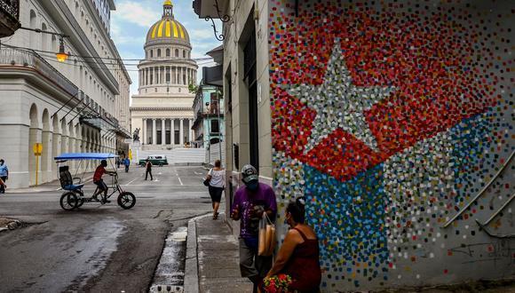 La gente habla cerca de un grafiti con la bandera cubana en una calle de La Habana, el 12 de julio de 2021. (Foto de YAMIL LAGE / AFP).