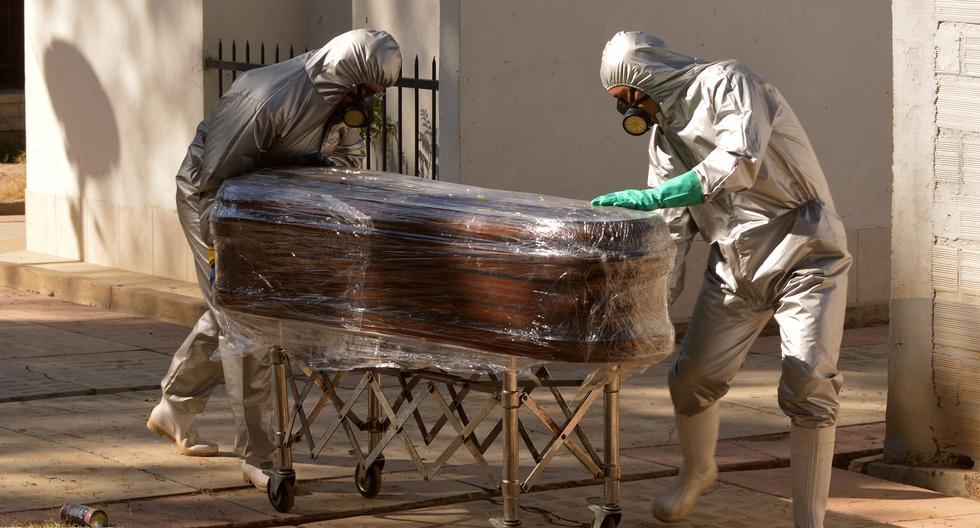 Trabajadores transportan el ataúd de una víctima de COVID-19 para ser enterrado en una fosa común en el cementerio general de Cochabamba. (Foto; Diego CARTAGENA / AFP)