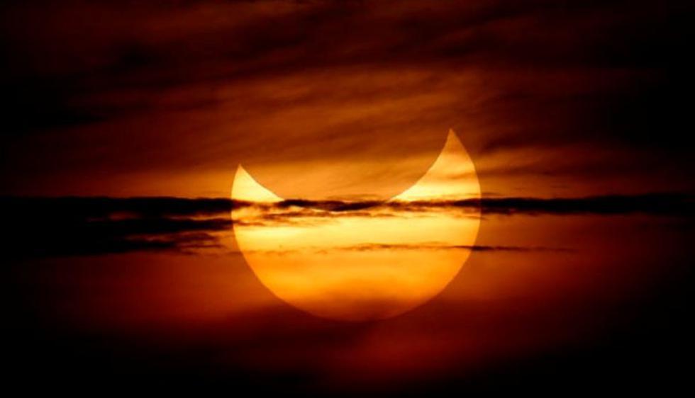 Un eclipse solar se convierte en  una amplia sonrisa naranja en Gumaca, Filipinas.