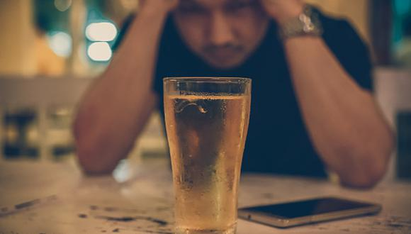 Asian young man in lonely and depressed action and holding head in hands and see glass of beer in pub and restaurant with low light place, depression and drinking concept