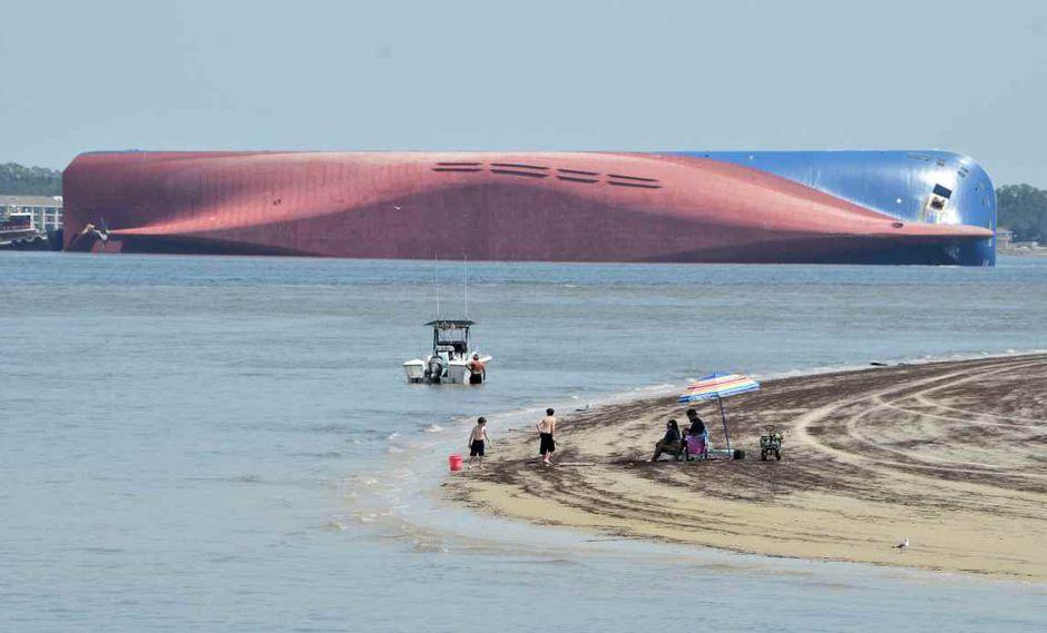 Un grupo de personas observa el buque de carga desde la Jekyll Island Driftwood Beach. (AP)