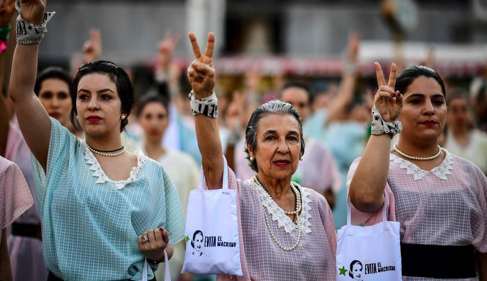 Disfrazados con vestidos de tonos pasteles típicos de 1930 y un moño emulando a Eva Perón, hombres y mujeres saltaron y bailaron esta semana en la plaza del Congreso argentino.  (Foto: AFP)