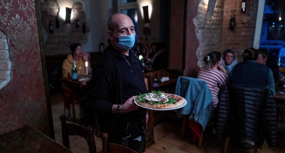 Imagen referencial. Un camarero, que usa una máscara facial por el coronavirus, sirve una pizza en Pepenero, un restaurante italiano en Alemania. (AFP / John MACDOUGALL).