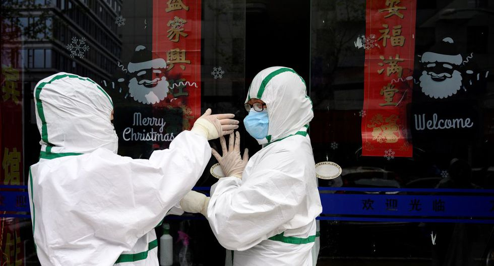Los trabajadores médicos que usan trajes de materiales peligrosos cierran una puerta de una clínica de pruebas para el nuevo coronavirus en Wuhan, en la provincia central de Hubei de China. (Foto: AFP/Noel Celis)