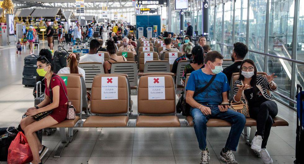 Las personas que usan máscaras faciales se sientan en los asientos con letreros que indican a los viajeros dónde pueden sentarse, para observar las reglas de distanciamiento social en medio de las preocupaciones sobre la propagación del coronavirus, en el aeropuerto de Suvarnabhumi en Bangkok. (Foto: AFP/Jack Taylor)