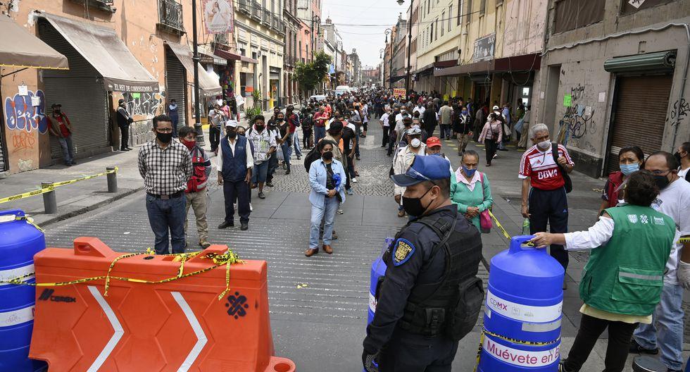 La policía y los trabajadores del Gobierno de la ciudad se encuentran en un control peatonal que limita el acceso en grupos de 20 personas para ingresar al centro de la Ciudad de México. (Foto: ALFREDO ESTRELLA / AFP)